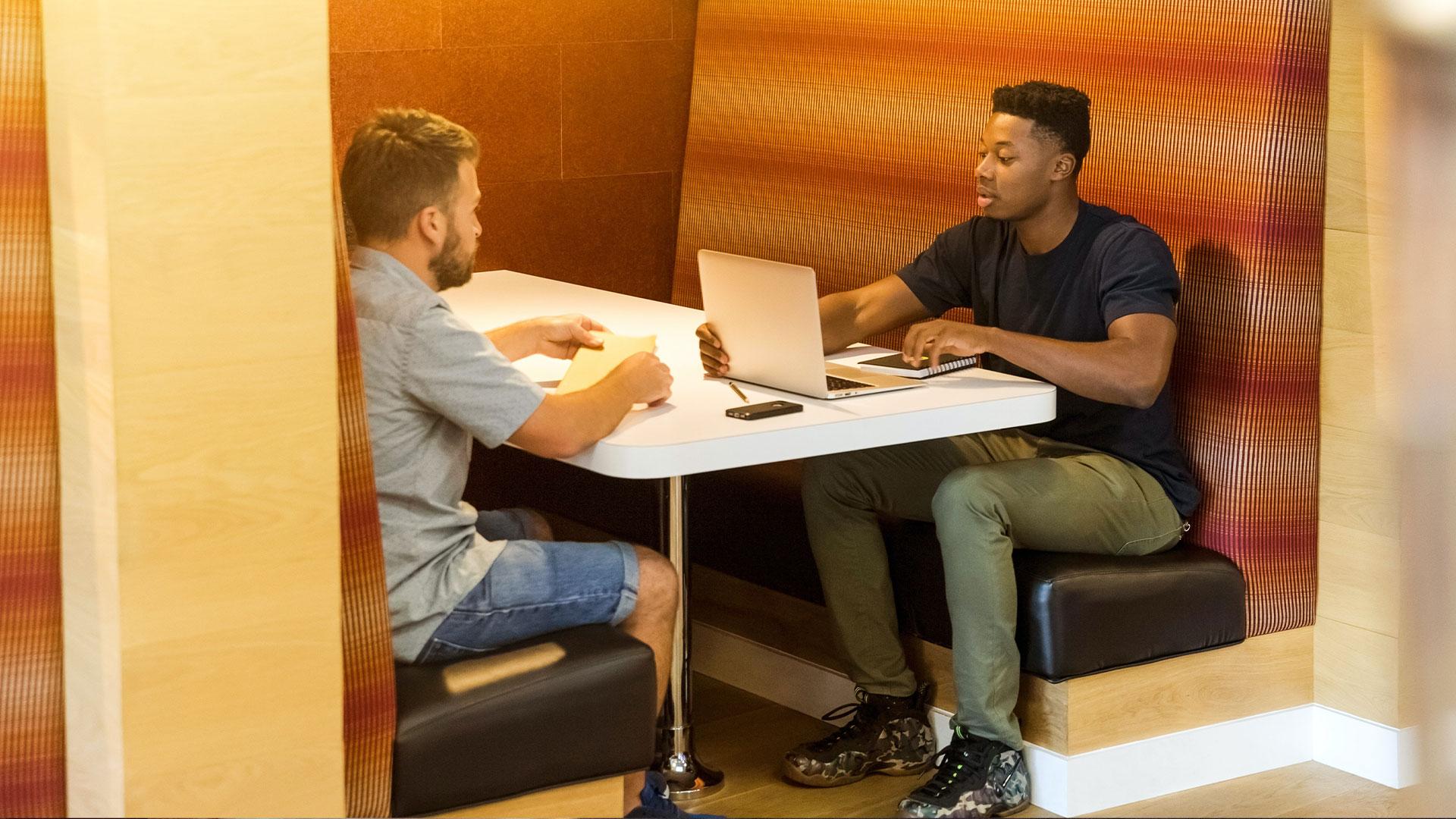 Kaksi opiskelijaa istuu ja juttelee
